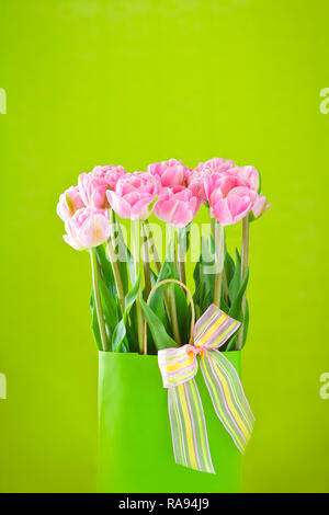 Flower bouquet of pink tulips in a vase with a multicolored bow tie on a bright green background, copy or text space - Stock Photo