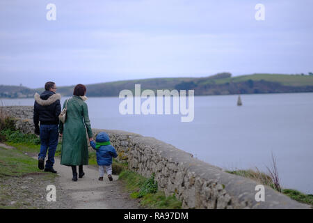 A family walking along a path in Cornwall, UK. - Stock Photo