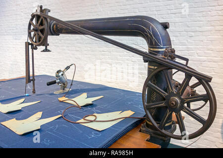Drawn patterns on fabric ready to be cut by 20th century industrial cloth cutting machine in textile factory at MIAT / Industriemuseum, Ghent, Belgium - Stock Photo