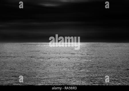 Wide minimalist view of ocean glistening in the horizon - Stock Photo