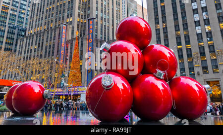 Giant Red Christmas Ornaments near Radio City Music Hall on 6th Avenue, New York City. - Stock Photo