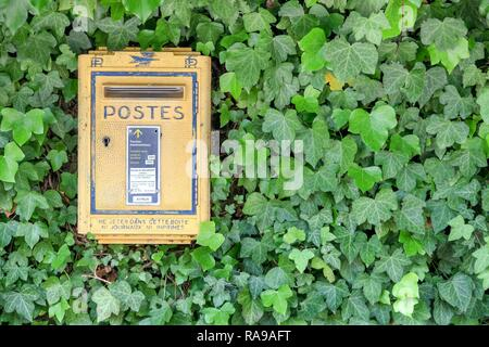 Brancion, France - June 1, 2015: Old and vintage yellow french letterbox in France, the french public postal service - Stock Photo