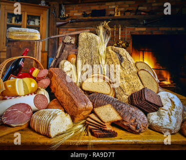 Still life of commercial food photography of german bread and meets in fron to a old country home wiith burning fireplace. - Stock Photo