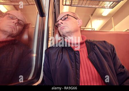 Middle age man looking out of the window of train. Passenger during travel by high speed express train in Europe. Elderly man travelling in train at night - Stock Photo