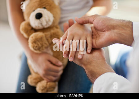 Doctor examining the hands of a young patient. - Stock Photo