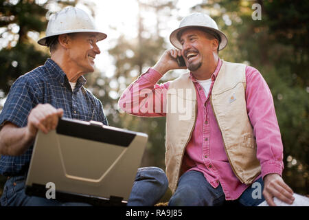 Two lumberjacks in the forest, one on his cellphone the other using his laptop. - Stock Photo