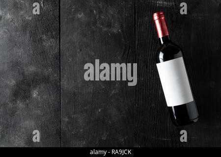 Red wine bottle on dark wooden table flat lay from above with copy space - Stock Photo