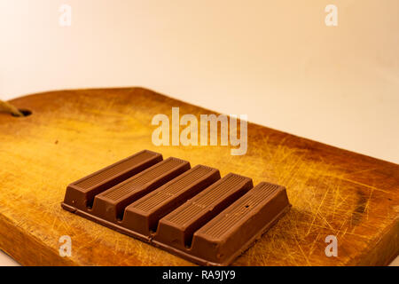 Chocolate bars on a rustic wooden board. Sweet food - Stock Photo