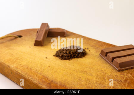 Chocolate bars, coffee and sugar on a rustic wooden board. Sweet food - Stock Photo