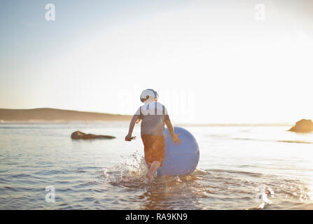 Young boy rolling a swiss ball in the surf at a beach. - Stock Photo