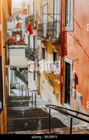 Portuguese old street. Hanging laundry at Sunset in the historical downtown of Lisbon, cityscape of Lissabon. - Stock Photo
