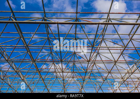 Urban abstract texture background. Point of view looking up in blue sky through old rusty geometric diagonal metal constructions of abandoned building - Stock Photo