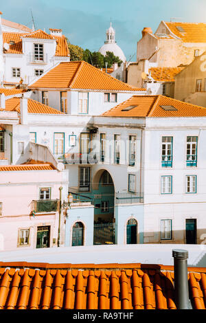 Colorful red and white citycape of Lisbon. Historical downtown built on the side of the hill. Bright sunny summer day. - Stock Photo