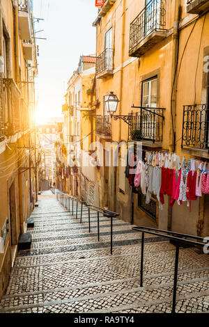 Staircase in the cobblestone street in Lisbon. Hanging laundry in typical narrow street. Sunset in the old downtown of Lisbon, impressions of the city - Stock Photo
