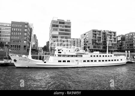 Hamburg, Germany - September 07, 2017: River transport, transportation. Ship at ferry pier on cityscape background. Water travel, travelling trip Vacation discovery wanderlust - Stock Photo