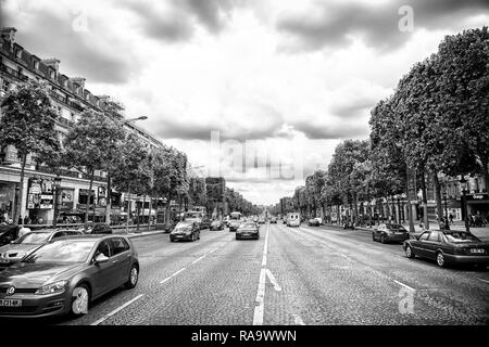 Paris, France - June 02, 2017: Avenue des Champs Elysees with busy traffic. Elysian fields road on cloudy sky. Vacation and travel in french capital. - Stock Photo