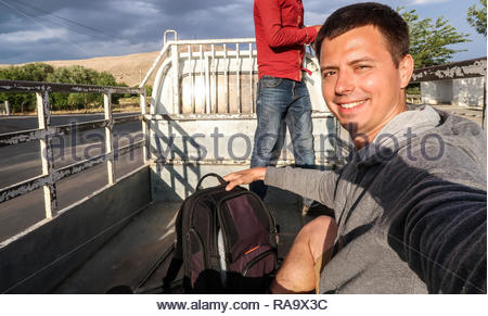 Selfie of a Young Man Traveling Around Uzbekistan in a Back Side of a Truck After Being Picked Up on the Road as a Hitchhiker - Stock Photo