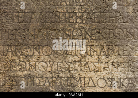 Real ancient letters cutted in stony wall of ancient architecture found during excavations of ancient ruin. Horizontal color photography