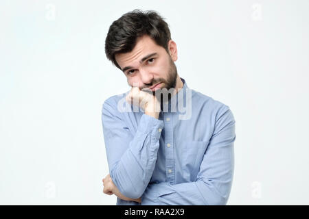 Man with beard holding hand on cheek looking tired and sick - Stock Photo
