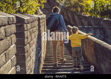 Happy cheerful joyful tourists dad and son at Great Wall of China having fun on travel smiling laughing and dancing during vacation trip in Asia. Chinese destination. Travel with children in China concept - Stock Photo