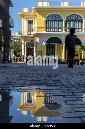 Colonial building of Plaza Vieja reflected in puddle - Stock Photo