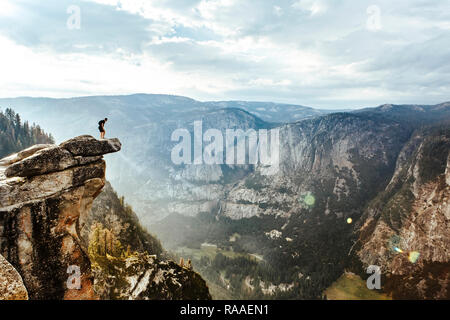 A fearless hiker is standing on overhanging rock at Glacier Point enjoying the view over Yosemite Valley, Yosemite National Park, California, USA - Stock Photo