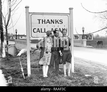 A lucky man has a flapper on each arm at the city limits, ca.1925. - Stock Photo