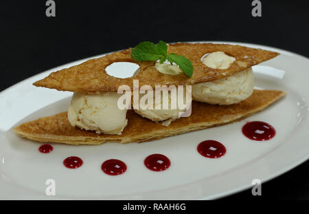 vanilla ice cream, crispy tuile, raspberry sauce - Stock Photo