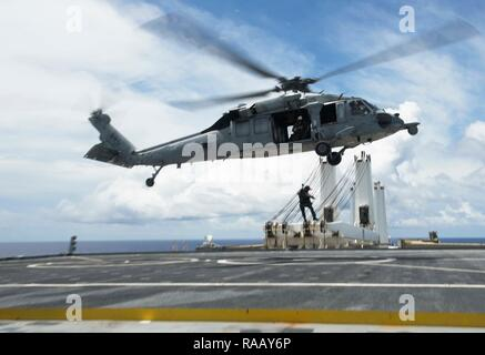 PACIFIC OCEAN (August 23, 2018) - Naval Air Crewman (Helicopter) 2nd Class Jacob Ward, acting crew chief and rescue swimmer assigned to Helicopter Sea Combat Squadron 25 (HSC-25), lowers Hospital Corpsman 2nd Class Kyle Bowen, a search and rescue medical technician assigned to HSC-25, onto the flight deck of the Watson-class vehicle cargo ship USNS Dahl (T-AKR-312) from HSC-25 MH-60S Seahawk helicopter during a medical evacuation drill, August 23. HSC 25 is the Navy's only forward deployed MH-60S expeditionary squadron. As a part of Helicopter Sea Combat Wing Pacific, it provides an armed heli - Stock Photo