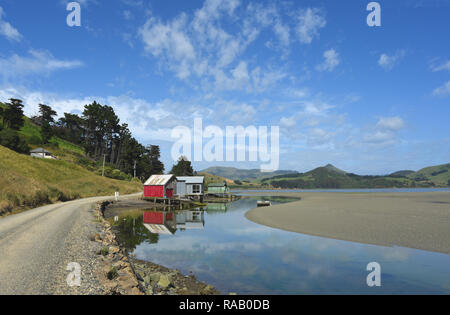 Amazing reflections of colorful ancient boat houses on the Otago peninsula of the South island of New Zealand. - Stock Photo