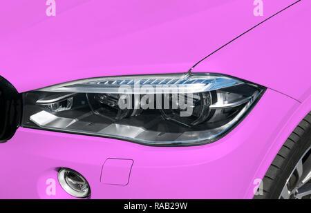 Headlight of a modern pink sport car. The front lights of the car. Modern Car exterior details - Stock Photo