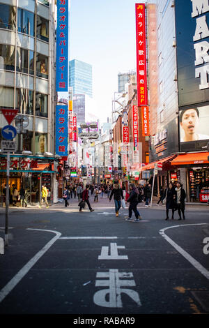 Some tourists stroll through the streets of Akihabara in Tokyo. - Stock Photo