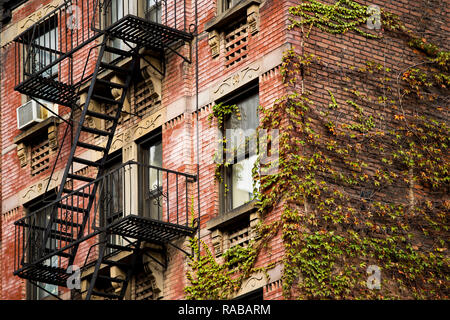 Close-up view of New York City style apartment buildings with emergency stairs along Mott Street in Chinatown neighbourhood of Manhattan, New York. - Stock Photo