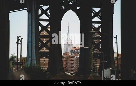 Spectacular view of the Empire State Building seen through the Manhattan bridge in Dumbo neighborhood. - Stock Photo