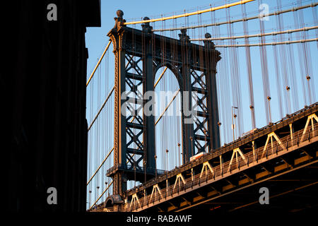 Close-up view of the Manhattan bridge seen from a narrow alley during the sunset. Manhattan, New York City, USA. - Stock Photo