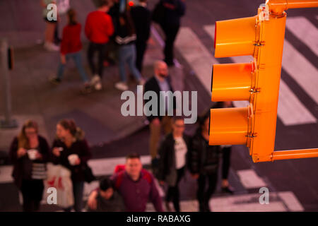 (focus on the traffic light) Close-up view of a traffic light and blurred people in the background crossing the street in Times Square, New York City, - Stock Photo