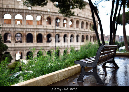 Spectacular view of the Coliseum with an empty bench in the foreground, Rome, Italy. - Stock Photo