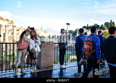 Some Chinese tourists are taking selfies in front of the beautiful Roman Forums in Rome, Italy. - Stock Photo