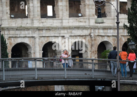 Some tourists are taking selfies in front of the beautiful Coliseum in Rome, Italy. - Stock Photo