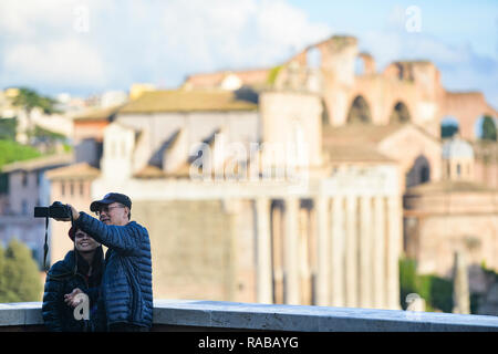 A couple of Chinese tourists are taking selfies in front of the beautiful Roman Forums in Rome, Italy. - Stock Photo