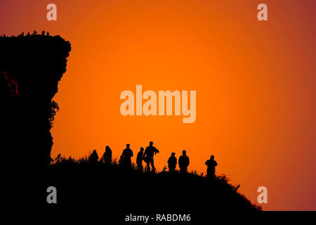 Silhouettes of so many people on top of the hills in the dark awaiting the sunrise. - Stock Photo
