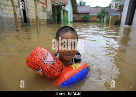 A child seen playing inside the water during a flood. Dozens of residents were evacuated due to the flood disaster that hit village Rancamaya Cikobak RT 03/04, Rancamaya, Bogor City. This flood began to hit dozens of houses in Kampung Rancamaya Cikobak due to the flow of the Cisadane tributary, the Cimakaci River overflowing. - Stock Photo