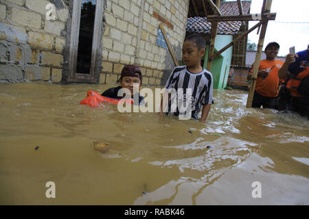 Bogor, West Java, Indonesia. 2nd Jan, 2019. Children are seen playing inside the water during a flood. Dozens of residents were evacuated due to the flood disaster that hit village Rancamaya Cikobak RT 03/04, Rancamaya, Bogor City. This flood began to hit dozens of houses in Kampung Rancamaya Cikobak due to the flow of the Cisadane tributary, the Cimakaci River overflowing. Credit: Adriana Adinandra/SOPA Images/ZUMA Wire/Alamy Live News - Stock Photo