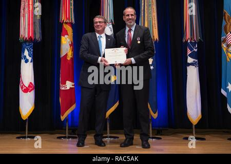 Defense Secretary Ash Carter recognizes the Under Secretary of Defense (Comptroller) and Chief Financial Officer, Hon. Mike McCord, with the Department of Defense Medal for Distinguished Public Service Award during a ceremony in the Pentagon Auditorium in Washington, D.C., Jan. 11, 2017. - Stock Photo