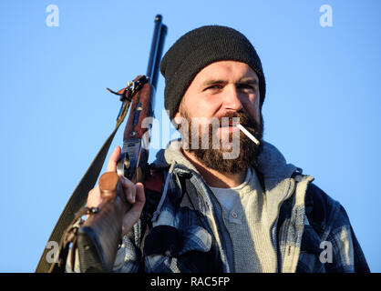 Guy bearded hunter spend leisure hunting and smoking. Hunting masculine hobby concept. Man brutal bearded guy gamekeeper blue sky background. Brutality and masculinity. Hunter with rifle gun close up. - Stock Photo
