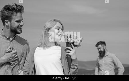 New love. Ex partner watching girl starts happy love relations. Couple in love dating outdoor sunny day, sky background. Ex husband jealous on background. Couple with flowers bouquet romantic date. - Stock Photo