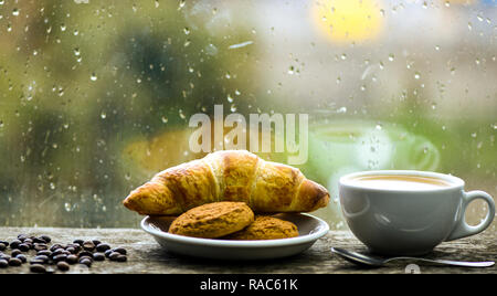 Enjoying coffee on rainy day. Coffee time on rainy day. Fresh brewed coffee in white cup or mug on windowsill. Wet glass window and cup of hot caffeine beverage. Coffee drink with croissant dessert. - Stock Photo