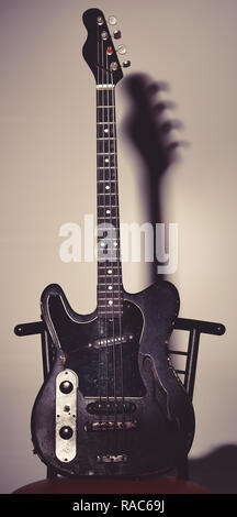 Musical instrument with four strings for playing metal or jazz music. Music and hard rock concept. Guitar in deep black color on black background with shadow. Electric guitar stands on dark chair. Stock Photo