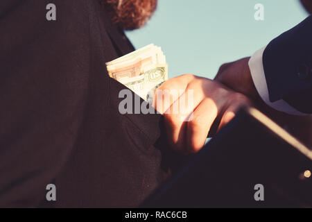 Man dressed in black suit holds folder takes bribe. Constructors make deal. Money, business and corruption concept. Manager puts money into pocket on blue sky background, close up. - Stock Photo