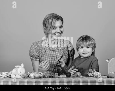 Family prepares for holiday on pink background. Easter and happy moments concept. Woman and little boy with smiling faces making decorations. Mother and son painting eggs for Easter. - Stock Photo